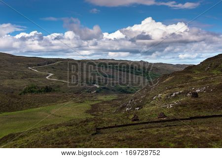 Assynt Peninsula Scotland - June 7 2012: Under blue and white sky over a green bare landscape the B869 road meanders over rocky hills and past pastures. Peat heaps upfront.
