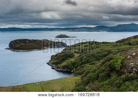 Assynt Peninsula Scotland - June 7 2012: View from higher up Drumbeg hamlet onto Atlantic Ocean under dark cloudy sky. Rocky islands with green patches gray seas and some vegetation upfront.