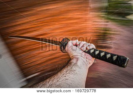 A hand brandishing an ornamental japanese sword.