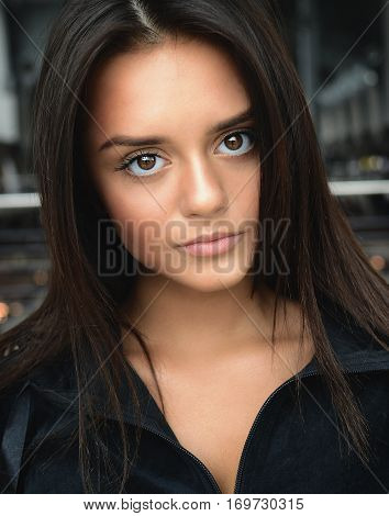 Close-up portrait of a beautiful young brunette girl with big eyes in casual comfortable clothes. Daily simple makeup. Huge eyes. Good vision. Lens.