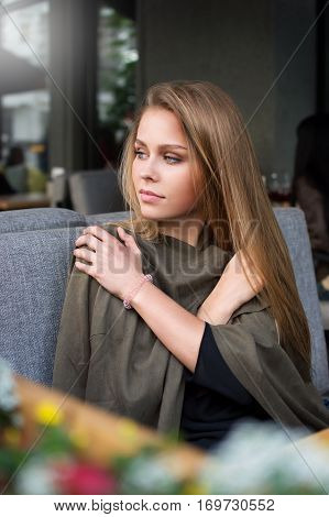 Charming girl hugging her arms while sitting at a cafe on the summer playground at lunchtime. Young woman sitting frozen in a bar on the street. Portrait.