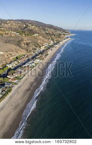 Aerial of large affluent beach homes along the sandy Pacific coast in Malibu California.
