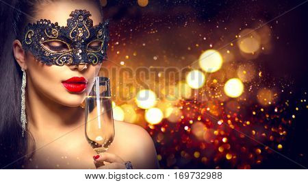 Beauty Glamour Woman celebrating with champagne, wearing carnival mask. party, drinking champagne over holiday glowing background. Christmas and New Year Holiday celebration.