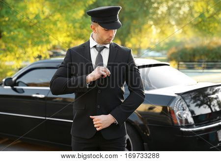 Young chauffeur adjusting suit near luxury car on the street