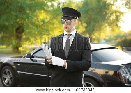 Young chauffeur adjusting gloves near luxury car on the street