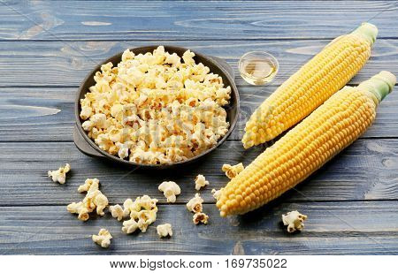 Pan with tasty traditional popcorn and corncobs on grey wooden background