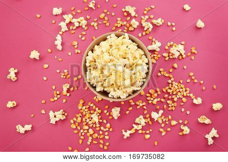 Bowl full of traditional popcorn on pink background