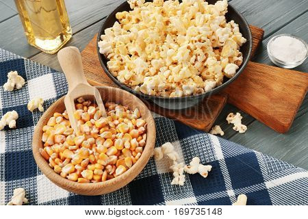 Pan full of traditional popcorn and bowl with corn grain on wooden table