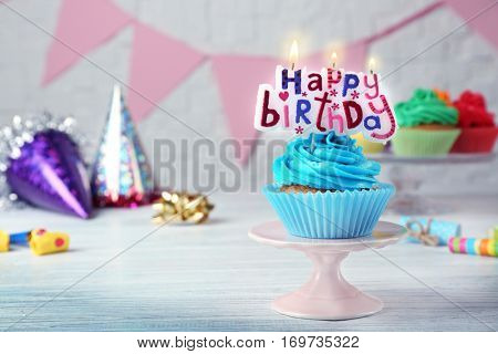 Birthday cupcake with party attributes on white table