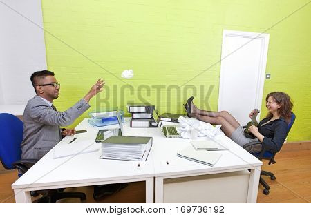 Colleagues throwing crumpled paper to each other