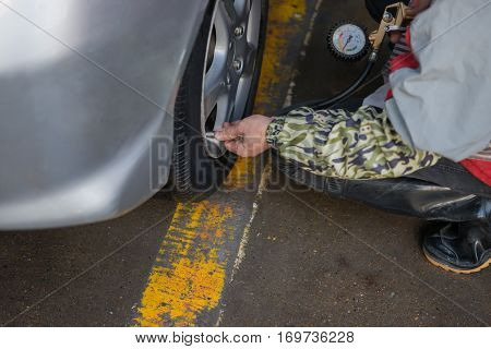 checking tire pressure with presure gauge and filling air