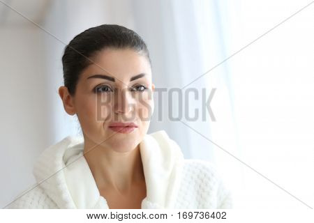 Adult woman checking her face in mirror on light background