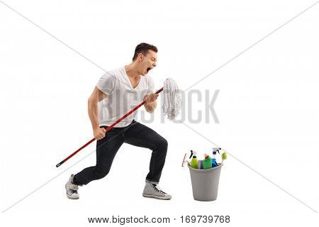 Full length portrait of a young man singing on a mop isolated on white background