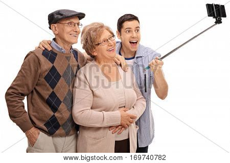 Cheerful seniors and a young man taking a selfie with a stick isolated on white background