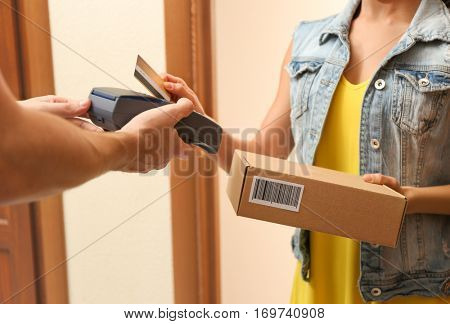 Young woman appending signature after receiving parcel from courier at home  (it's not real QR Code)