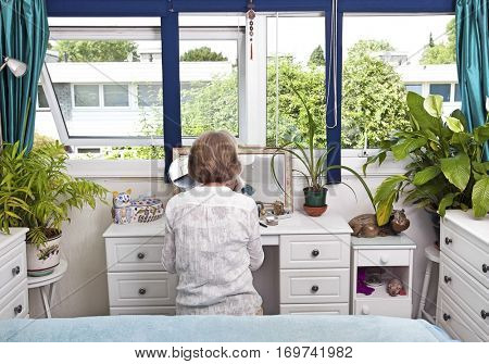 Rear view of woman sitting at dresser in bedroom