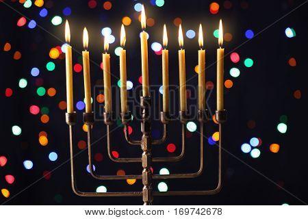 Menorah with candles for Hanukkah against defocused lights, close up