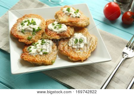 Plate with tasty potato pancakes for Hanukkah on wooden table