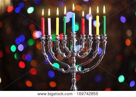 Menorah with candles for Hanukkah against defocused lights