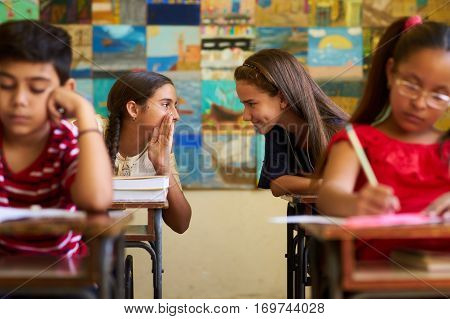 Young people and education. Group of hispanic students in class at school during lesson. Girls cheating during admission test examination