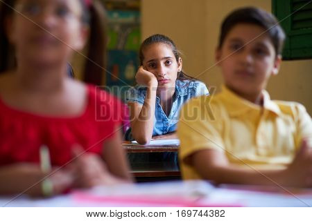 Young people and education. Group of hispanic students in class at school during lesson. Girl with anxiety bored female student