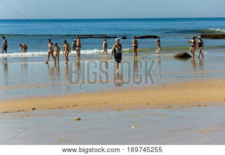 ALBUFEIRA, PORTUGAL - AUGUST 21, 2016: People at the beach of Olhos de Agua in Albufeira. This beach is a part of tourist region of Algarve.