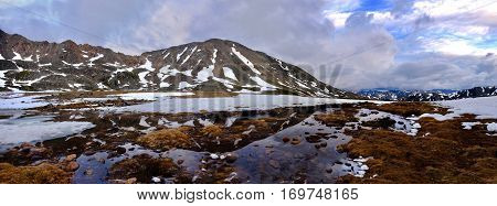 Panorama of mountanis and reflection in water. Snow thawing on Independence Pass. Aspen. Colorado. United States.