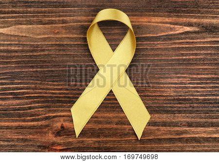 Golden ribbon on wooden background. Children cancer concept