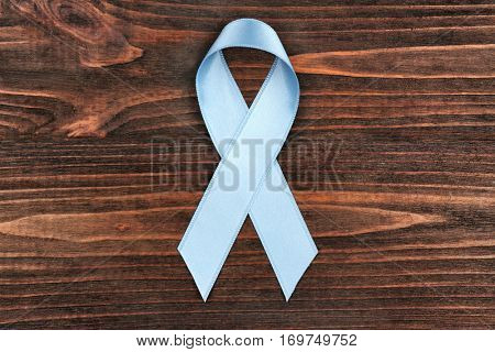 Light blue ribbon on wooden background. Prostate cancer concept