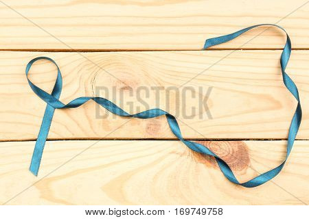 Sea-green ribbon on wooden background. Ovarian cancer and gynecological disorders concept