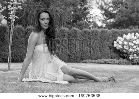 Full length of attractive young woman in sundress relaxing at park