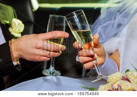 Womans and mans wedding hands with glasses. the couple holding glasses of champagne