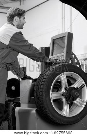 Side view of mid adult male mechanic repairing car's wheel in workshop