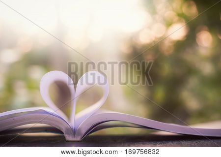 Book page in heart shape with natural light background