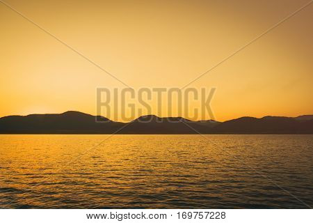sunset at the lake with mountains in the background