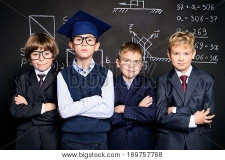 Educational concept. Group of smart schoolboys posing together in school uniform over blackboard.