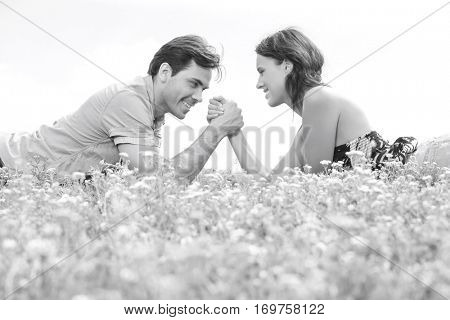 Side view of young couple arm wrestling while lying on grass against sky