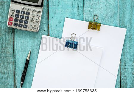 Blue Wooden Desk Table With Paper Ream, Pen, And Calculator.