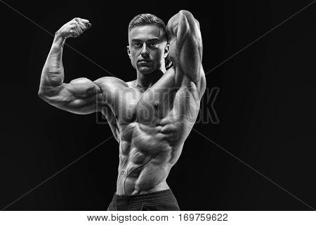Bodybuilder With Muscular Physique Looking At Camera Showing Biceps