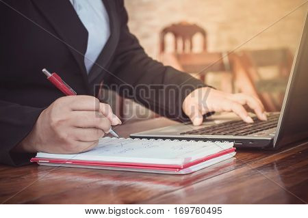 Close up of business woman's hand writing on a notebook