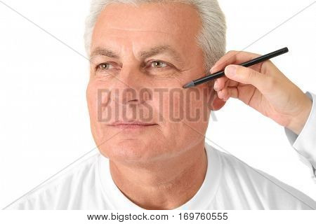 Female hand drawing correction line on man's face on white background