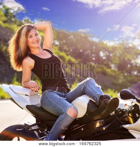 Young beautiful blonde girl in trendy jeans and a black t-shirt is resting on nature in seat of modern motorcycle. Outdoor portrait in soft sunny tones.