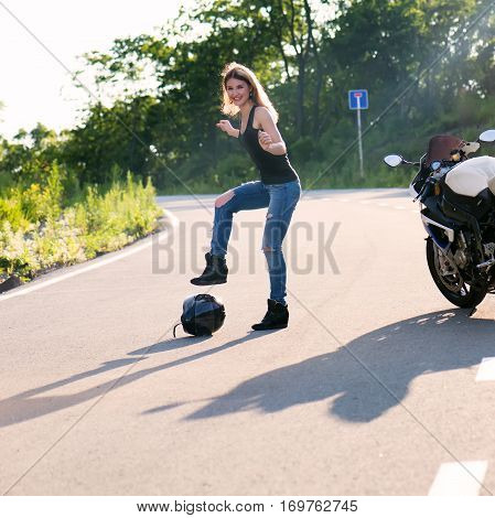 Young beautiful blonde girl in trendy jeans and a black T-shirt took off and put his helmet on the road near the modern motorcycle. Outdoor portrait in soft sunlight.