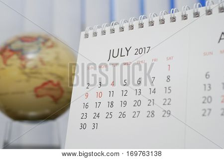 Close up calendar of July 2017 with blur earth globe background