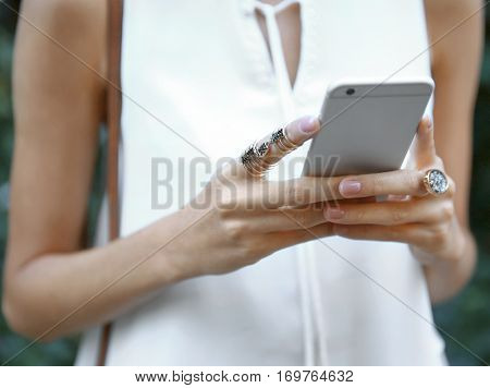 Female hands with phone and stylish rings, closeup