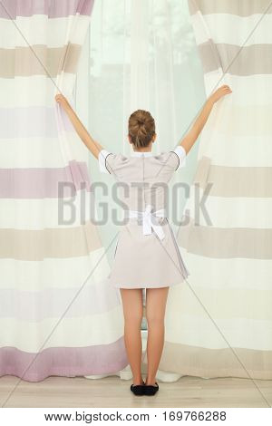 Hotel service concept. Chambermaid adjusting curtains in the room