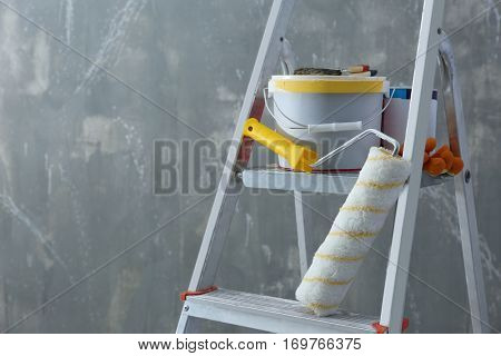 Ladder and set of tools for repair near grunge wall, closeup