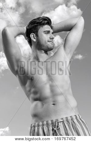 Shirtless young man with hands behind head against cloudy sky