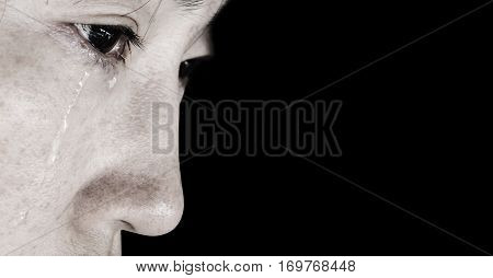 hopeless woman with tear on face on black