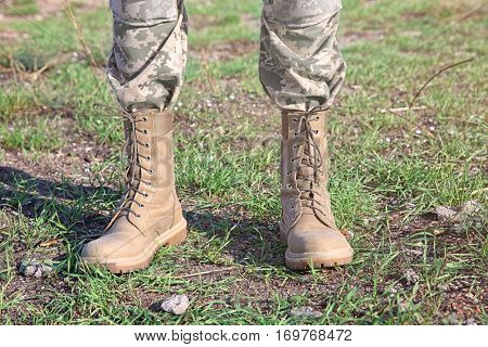 Feet of soldier standing at military firing range, close up view